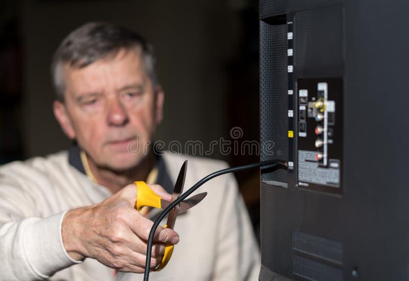 Hög man som klipper kabeln på hans kabel-TVpacke arkivbild