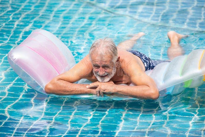 Hög man som kopplar av på den uppblåsbara luftmadrassen i simbassäng ta ett avbrott, vila, avgången, genomköraren, kondition, spo arkivbild