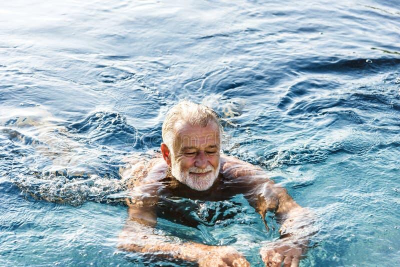 Hög man som kyler i simbassäng arkivbild