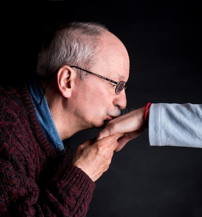 Hög man som kysser en woman& x27; s-hand royaltyfria bilder