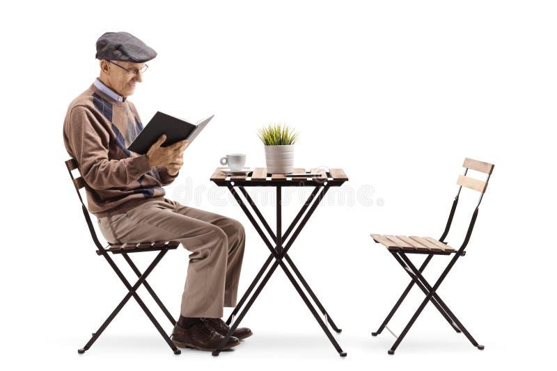 Hög man som läser en bok på en kaffetabell arkivbild