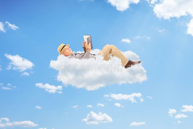 Hög man som läser en bok på moln royaltyfri fotografi