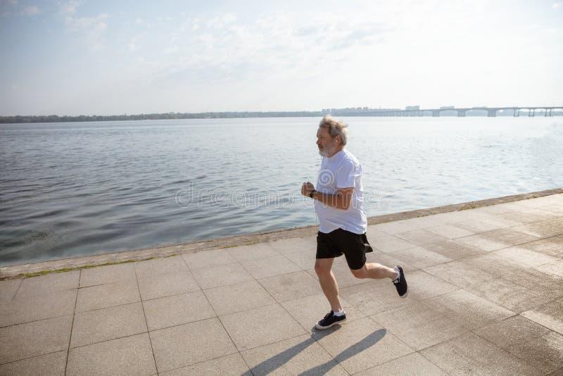 Hög man som löparen med armbindeln eller konditionbogserare på flodstranden royaltyfri foto
