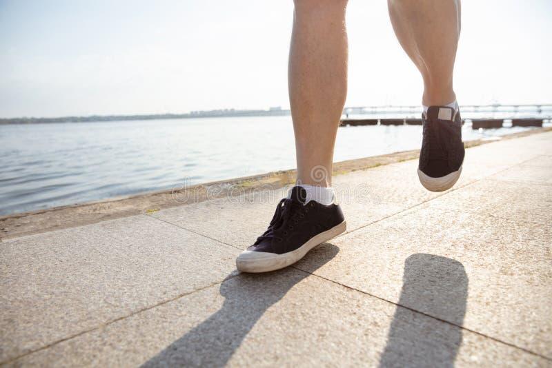 Hög man som löparen med armbindeln eller konditionbogserare på flodstranden arkivbilder