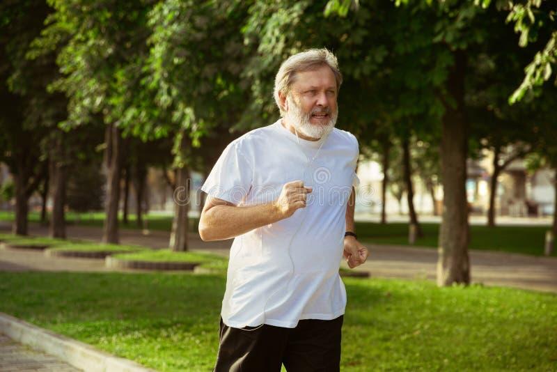 Hög man som löparen med armbindeln eller konditionbogserare på stadens gata royaltyfri foto