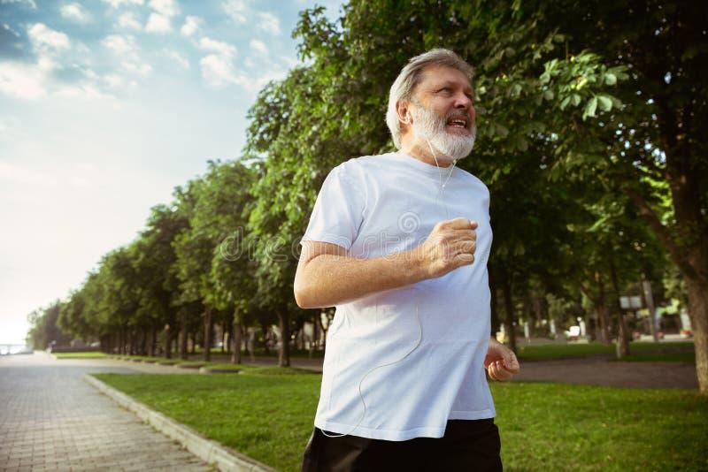 Hög man som löparen med armbindeln eller konditionbogserare på stadens gata fotografering för bildbyråer