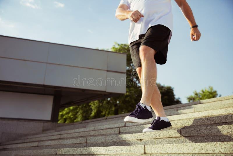 Hög man som löparen med armbindeln eller konditionbogserare på stadens gata arkivfoton