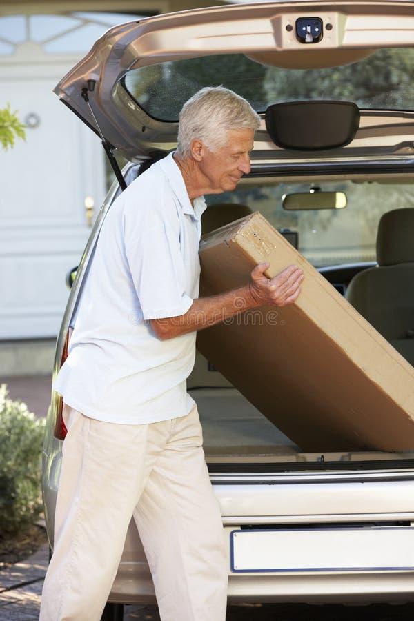 Hög man som laddar den stora packen in i baksida av bilen royaltyfria foton