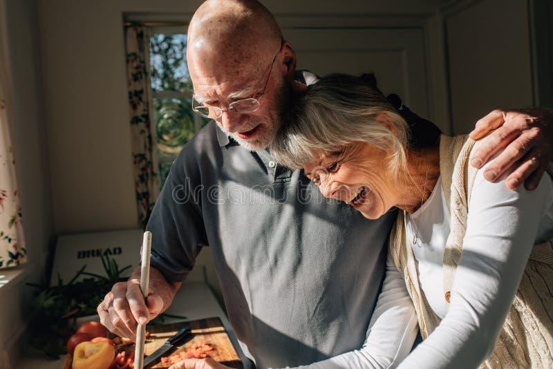 Hög man som lagar mat mat som rymmer hans fru i hans armanseende i kök Höga par som har bra tid som tillsammans lagar mat mat på arkivfoto