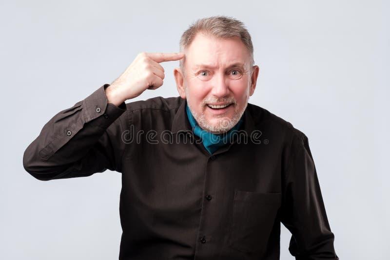 Hög man som ler att peka till huvudet med ett finger, stor idé eller tanke royaltyfria foton