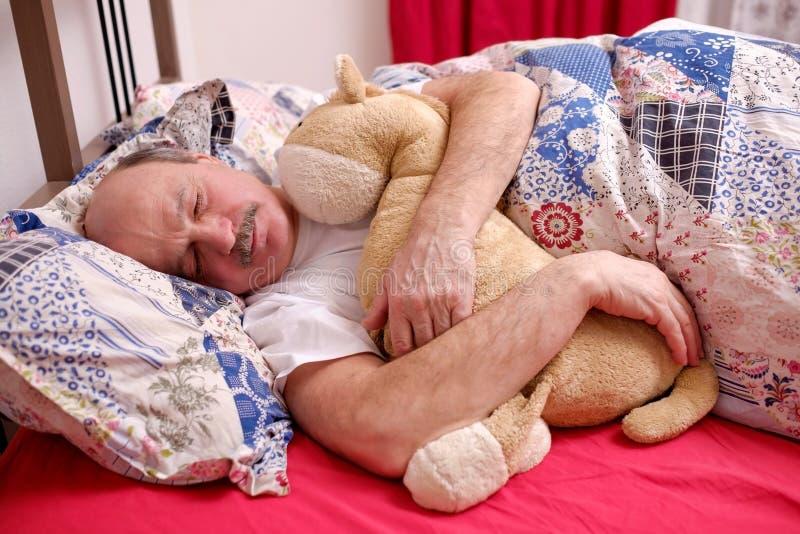 Hög man som ler medan sovande i morgonen, nöjd pensionär som ligger i säng arkivfoton