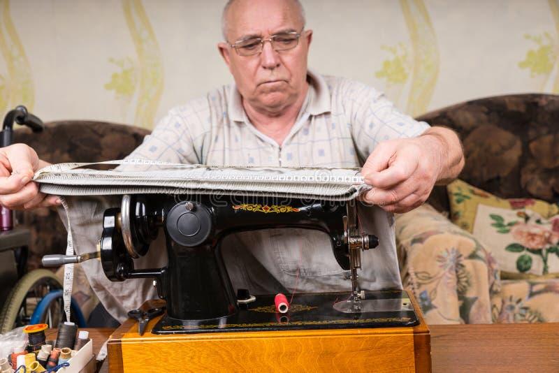 Hög man som mäter tyg på symaskinen royaltyfria foton
