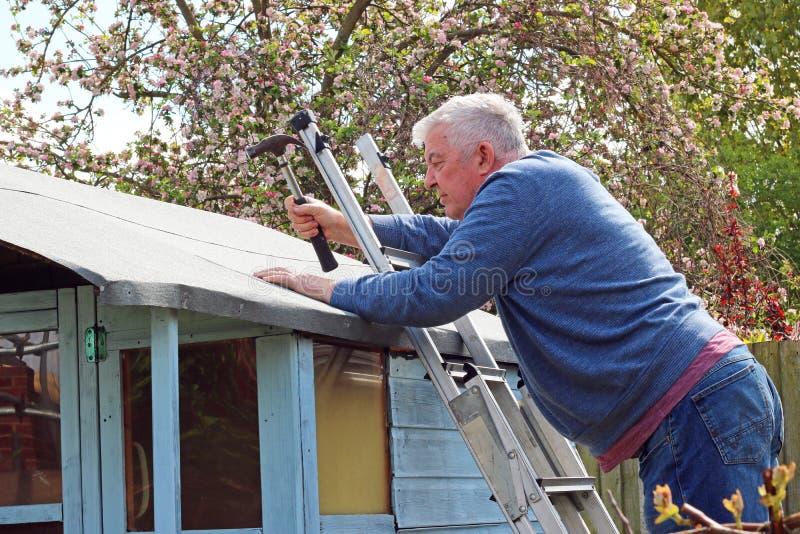 Hög man som reparerar det utgöt taket arkivfoton