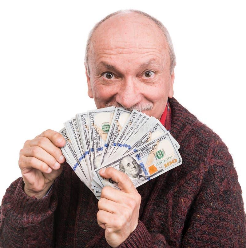 Hög man som rymmer en bunt av pengar Stående av en upphetsad gammal affärsman arkivfoto