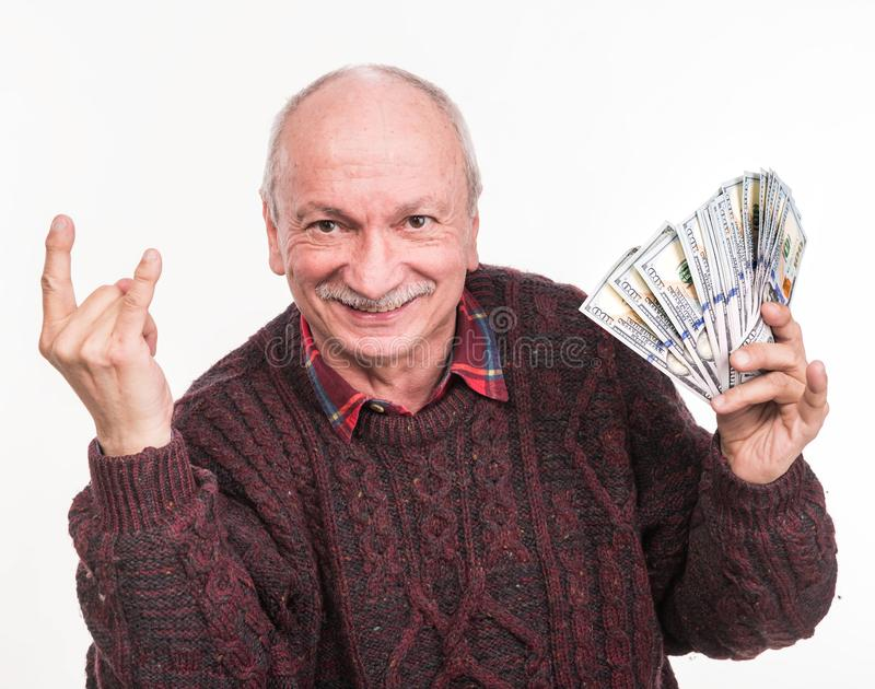 Hög man som rymmer en bunt av pengar Stående av en upphetsad gammal affärsman royaltyfria bilder