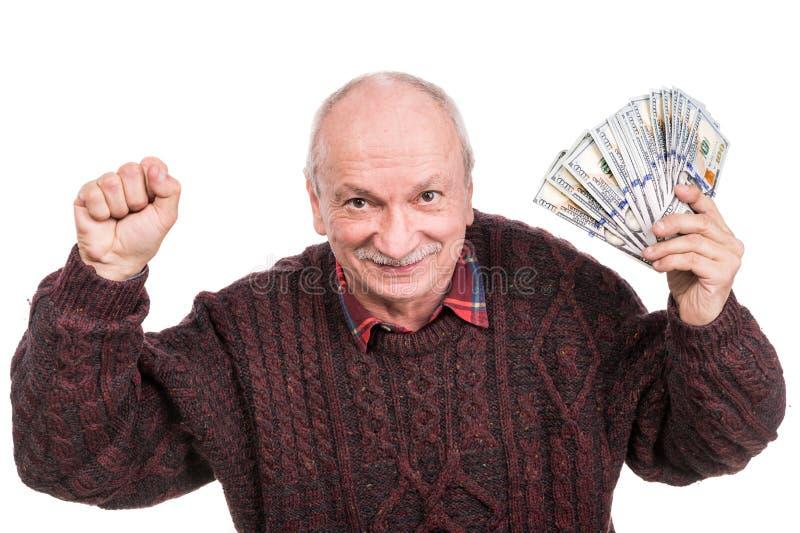 Hög man som rymmer en bunt av pengar Stående av en upphetsad gammal affärsman fotografering för bildbyråer