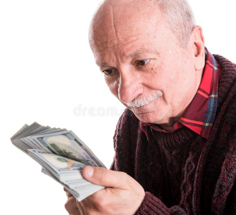 Hög man som rymmer en bunt av pengar Stående av en upphetsad gammal affärsman arkivbilder