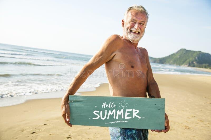 Hög man som rymmer en skylt på stranden arkivfoton