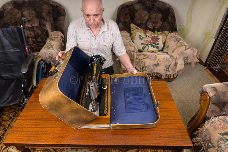 Hög man som sätter hans symaskin i ett fall arkivfoton