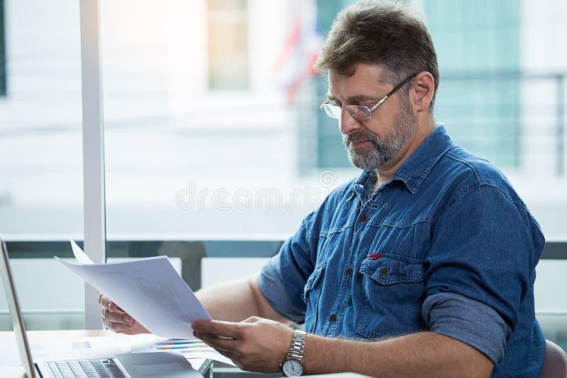 Hög man som ser dokument på skrivbordet royaltyfri bild