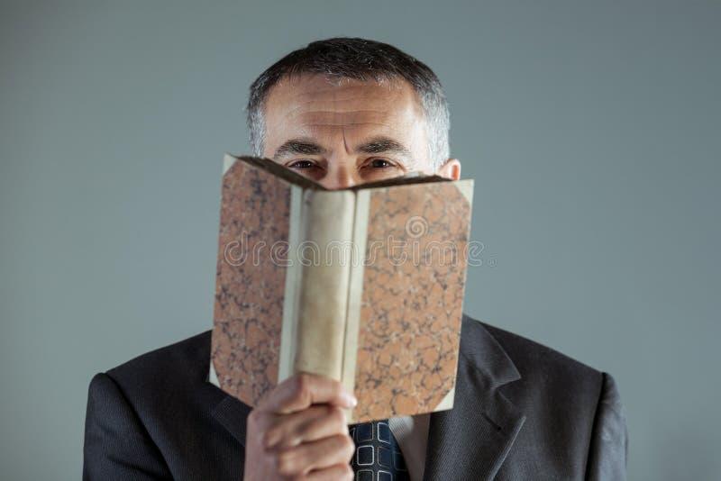 Hög man som ser kameran bak en gammal bok fotografering för bildbyråer