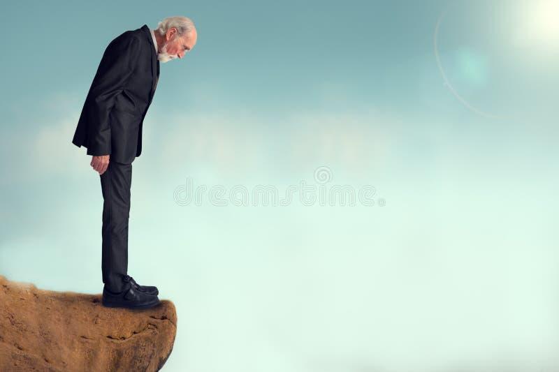 Hög man som ser ner från en klippa arkivfoto