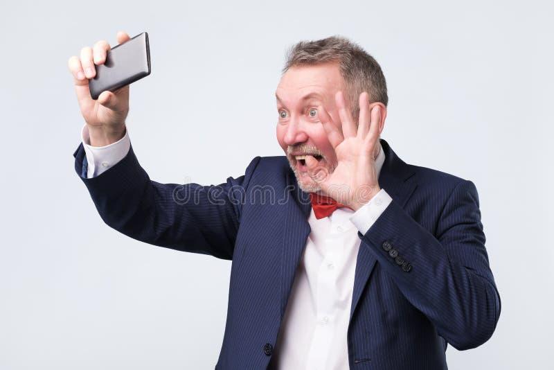 Hög man som ser skärmen av den smarta telefonen, vinkande hälsning som ha video pratstund arkivbilder