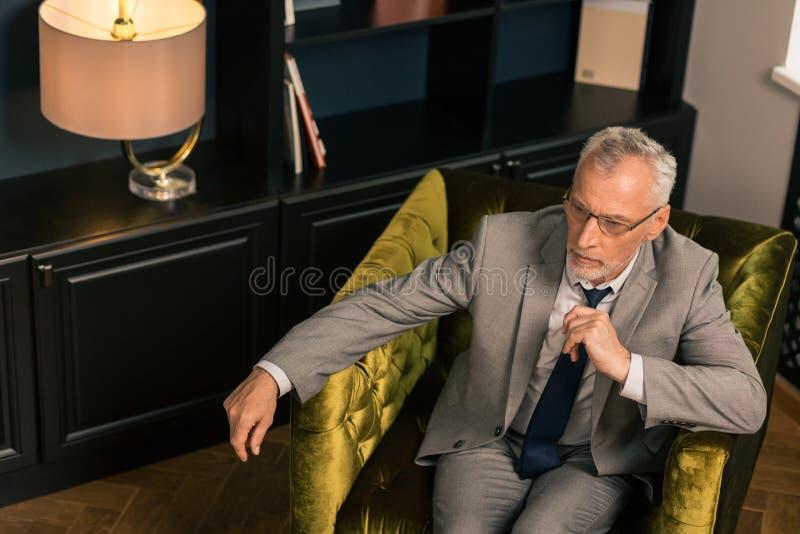 Hög man som sitter i en sammet stoppad fåtölj royaltyfri foto