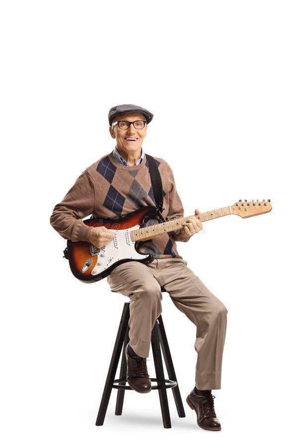 Hög man som sitter på en stol med en elektrisk gitarr arkivbild