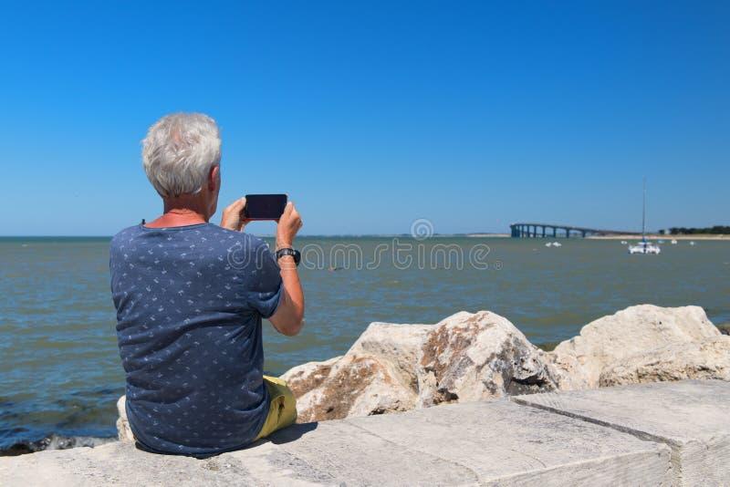 Hög man som sitter på kusten arkivfoto