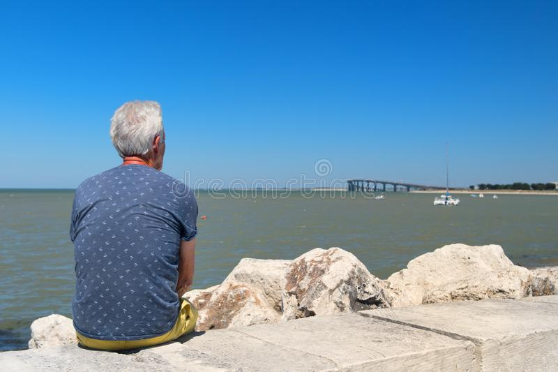 Hög man som sitter på kusten arkivbild