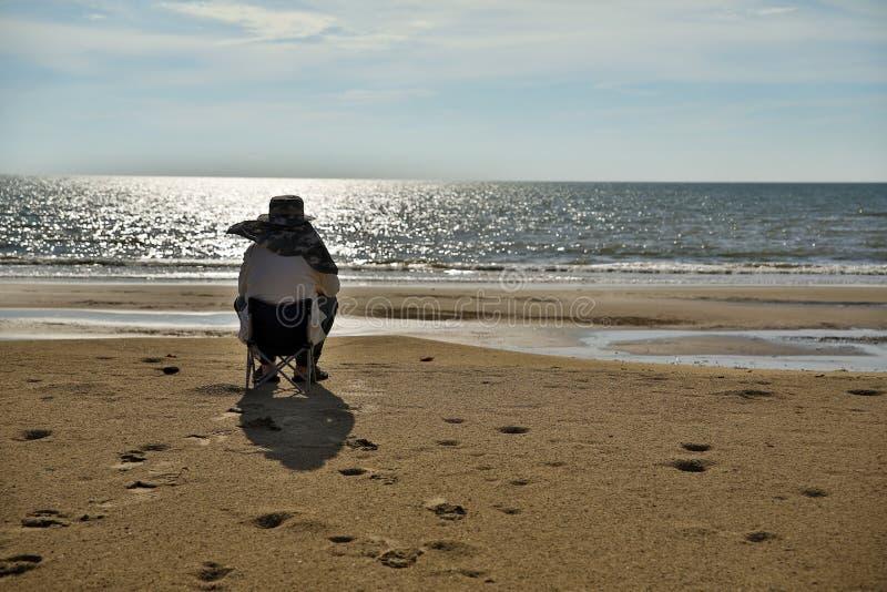 Hög man som sitter på stranden arkivfoto