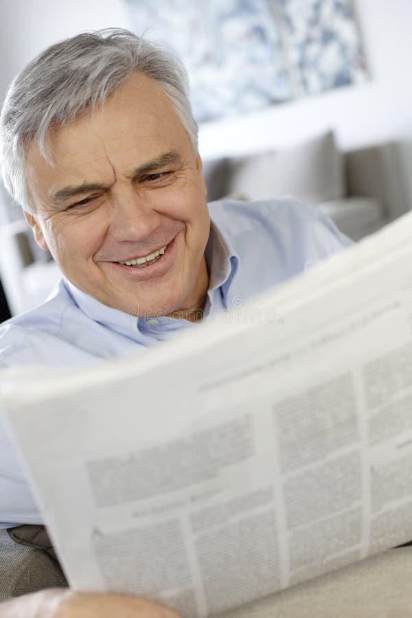 Hög man som skrattar den läs- tidningen fotografering för bildbyråer
