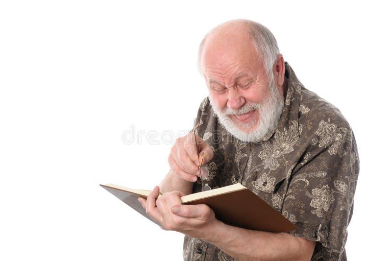 Hög man som skrattar, medan läsa en bok som isoleras på vit royaltyfria bilder