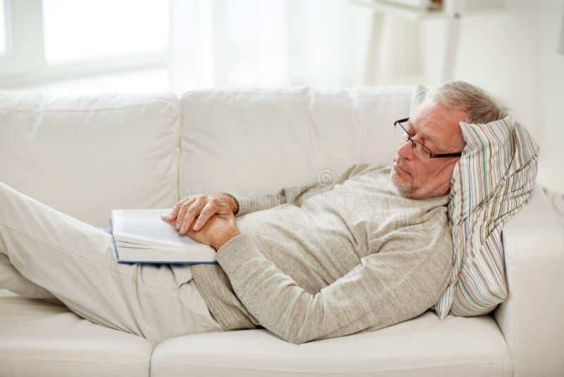 Hög man som sover på soffan med den hemmastadda boken royaltyfri fotografi