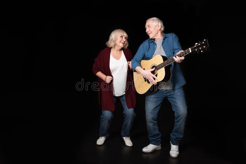 Hög man som spelar gitarren medan kvinna som nära dansar royaltyfri fotografi