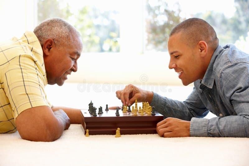 Hög man som spelar schack med sonen royaltyfria bilder