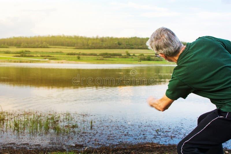 Hög man som spelar stenen som hoppar over på en sjö royaltyfria bilder