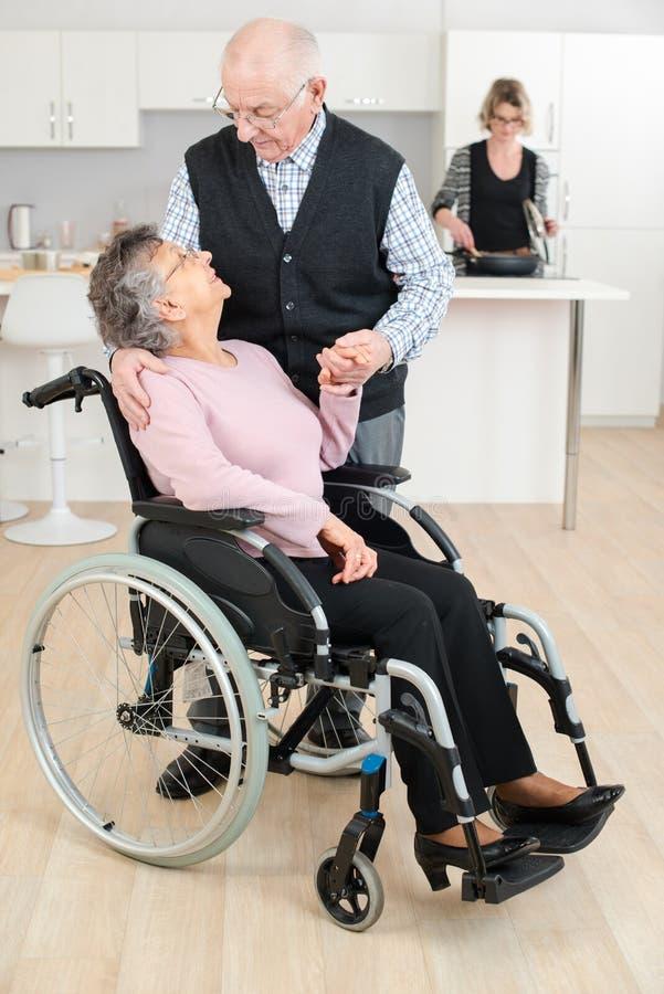 H?g man som trycker p? kvinnan i rullstol royaltyfri foto