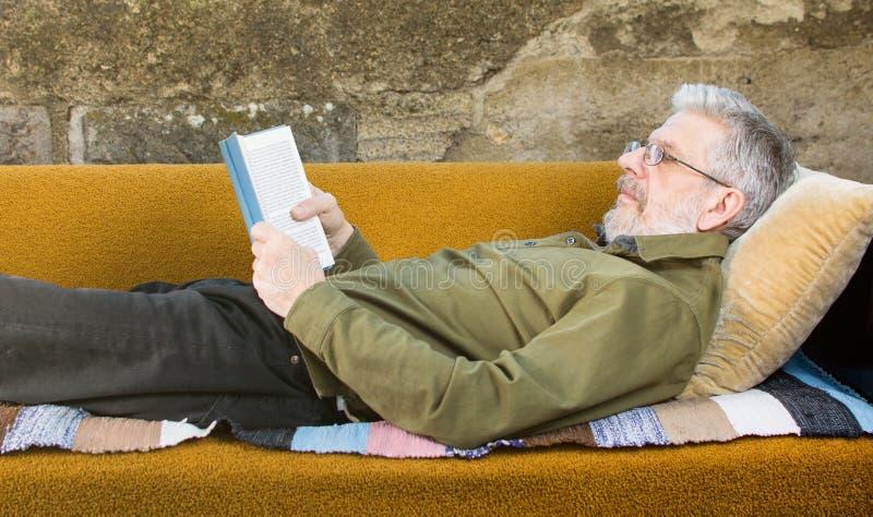 Hög man som utomhus läser en bok i soffasäng royaltyfri fotografi