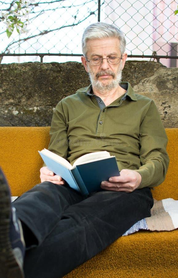 Hög man som utomhus läser en bok i soffasäng arkivfoto