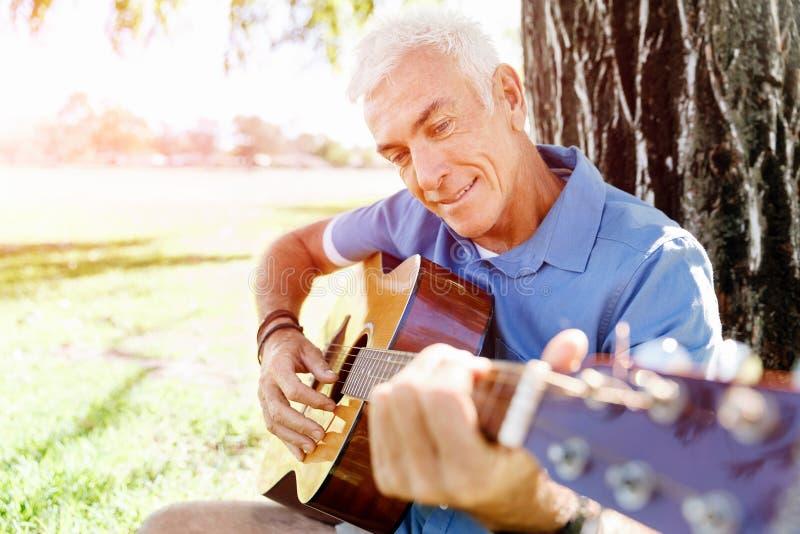 Download Hög Man Som Utomhus Plying Gitarren Arkivfoto - Bild av ferie, pensionär: 78729968