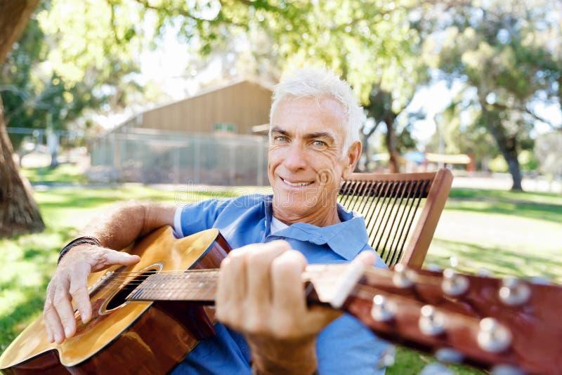 Download Hög Man Som Utomhus Plying Gitarren Fotografering för Bildbyråer - Bild av lycka, kamratskap: 78730221