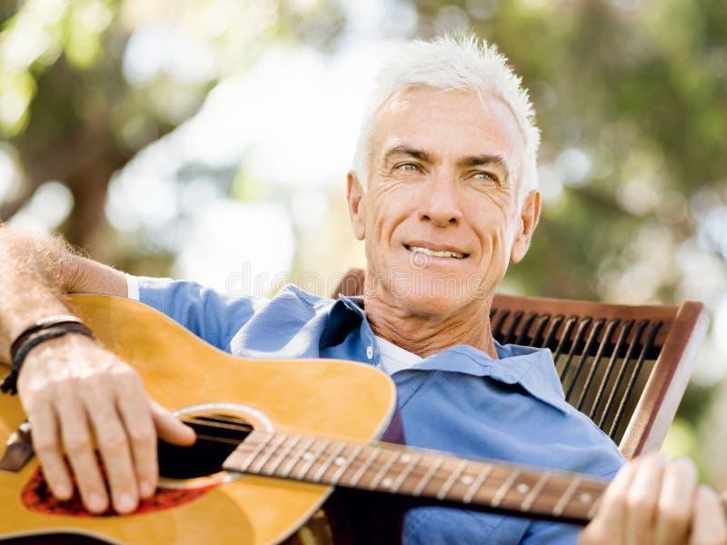 Download Hög Man Som Utomhus Plying Gitarren Arkivfoto - Bild av utomhus, lyckligt: 78730396