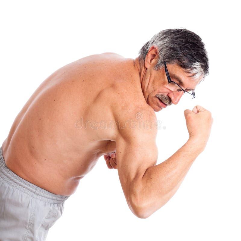 Hög man som visar bicepsen fotografering för bildbyråer