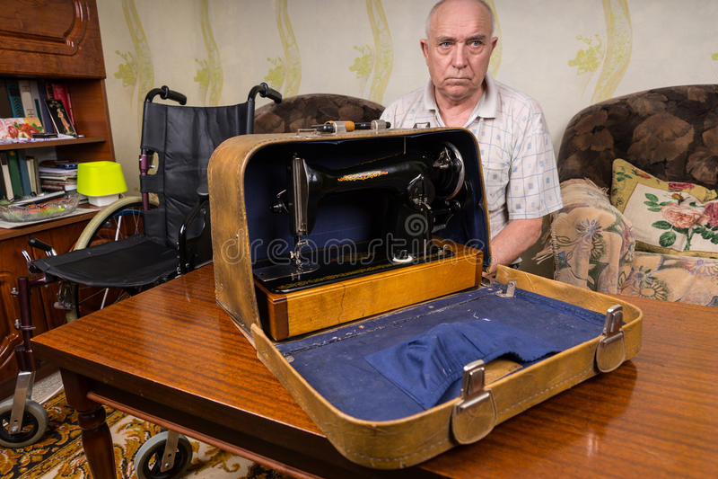 Hög man som visar hans symaskin i ett fall arkivbilder