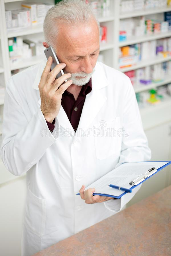Hög manlig apotekare som talar på telefonen och rymmer en skrivplatta royaltyfri foto