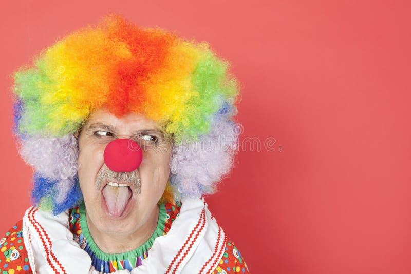 Hög manlig clown som ut klibbar tungan, medan se bort över röd bakgrund arkivfoto