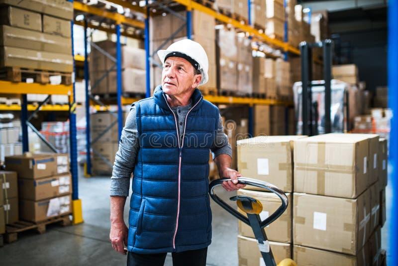 Hög manlig lagerarbetare som drar en palettlastbil royaltyfria foton
