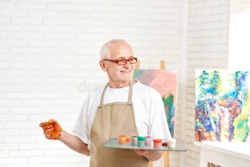 Hög manlig målare som står med paletten av färger i hand på studion royaltyfria bilder
